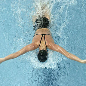 Woman swimming butterfly shot from above.
